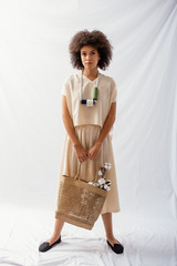 Fashion Model With Afro Hairstyle Holding A Bag With Raw Cotton Buds