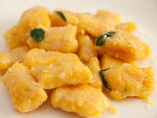 Pumpkin gnocchi with sage and butter on a white plate