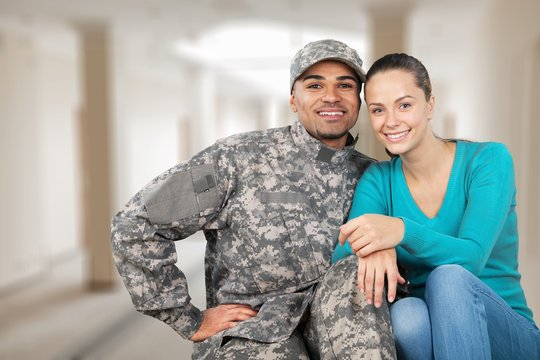 Smiling soldier with his wife standing against  background