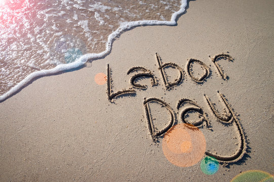 Labor Day message handwritten on the smooth sand of an empty beach with sunny lens flare across an oncoming wave
