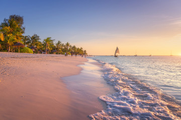 Obraz Sandy beach with sea waves, palm trees and walking people at colorful sunset in summer.  Tropical landscape with blue sea, palms, boats and yachts in ocean, beautiful sky. Travel in exotic Africa - fototapety do salonu