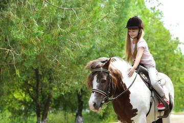 Cute little girl riding pony in green park Papier Peint