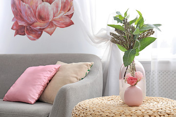 Vases with beautiful bouquets on table in room interior
