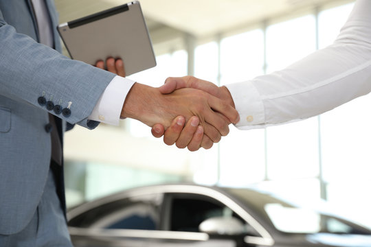 Young salesman shaking hands with client in modern car dealership, closeup