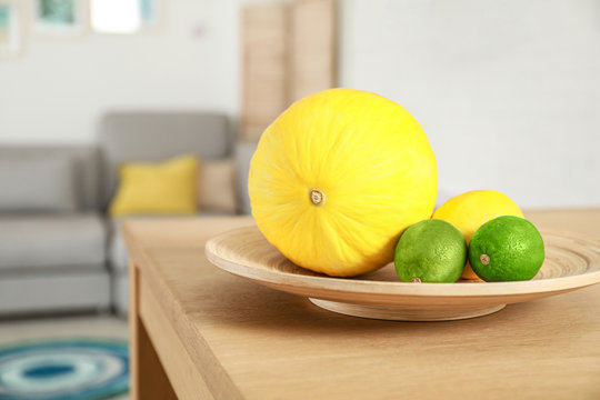 Plate of ripe fruits on wooden table in living room interior