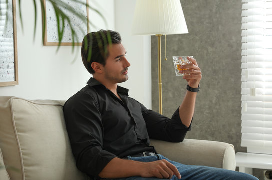 Young man with glass of whiskey at home