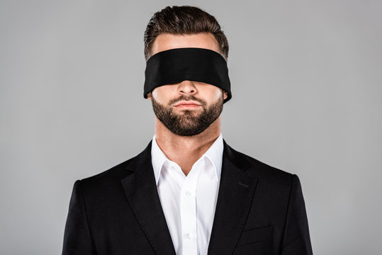 bearded handsome blindfolded businessman in black suit isolated on grey