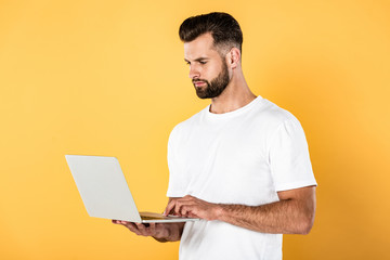 man in white t-shirt using laptop isolated on yellow