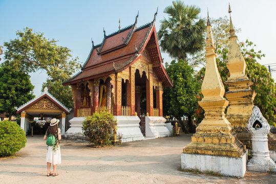 Woman visiting Wat Sensoukaram one of the most popular temple in Luang Prabang, Laos.