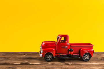 Red toy truck on bright yellow background.