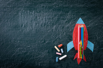 Education or back to school Concept. Top view of Painted paper rocket with colorful of color pencil and chalk on chalkboard background. Flat lay.