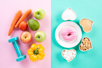 Healthy lifestyle, food and sport concept. Top view of healthy versus unhealthy. Donut and various types of sugar VS fruit vegetables, measuring tape and dumbbell on pink blue pastel background.