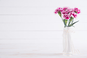 Valentines day and love concept. Pink carnation flower in vase on white wooden background.