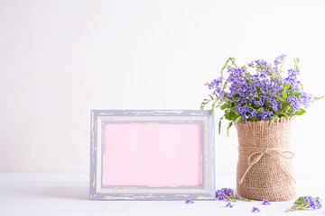 White picture frame with lovely purple flower in vase on white wooden table.