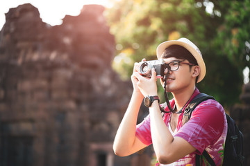 Young Man Photographer Traveler with backpack taking photo with his camera, Great wall in background at historical place. Lifestyle and travel concept.