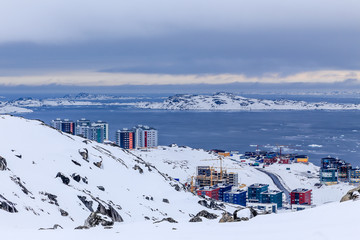 Arctic streets and building blocks of greenlandic capital Nuuk city at the fjord, view from snow hills, Greenland