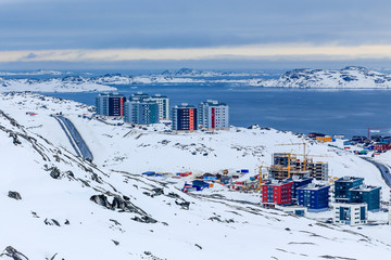 Streets and building blocks of greenlandic capital Nuuk city at the fjord, view from snow hills, Greenland