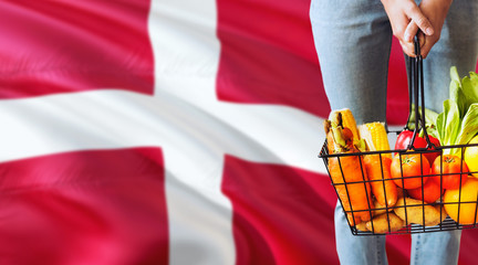 Woman is holding supermarket basket, Denmark waving flag background. Economy concept for fresh fruits and vegetables.