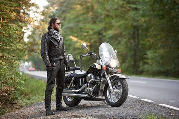Bearded tall athletic motorcyclist in dark sunglasses, black leather jacket and gloves standing at shiny modern powerful cruiser motorbike on blurred background of hilly asphalt road and green trees.