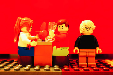 Lego man and woman having a date by a table with drinks. Angry male standing on the right side on February 4, 2019 in Poznan, Poland.