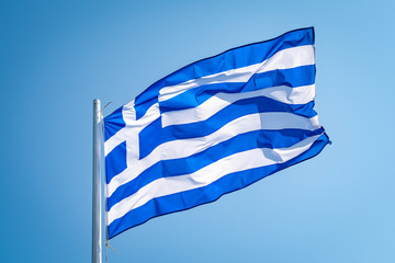 Flag of Greece waving in the wind in front of blue sky.