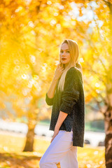 Fall concept - beautiful woman drinking coffee in autumn park under fall foliage