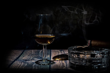 Glass of whiskey and cigar on black background