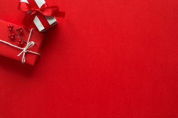 Christmas gifts presents on red background. Simple, classic red and white wrapped gift boxes with ribbon bows and festive holiday decorations Fototapete