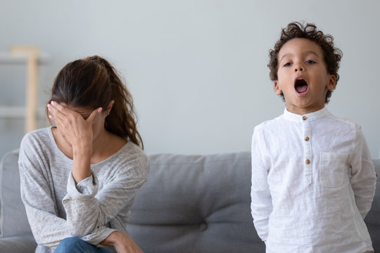 Stressed upset mother tired about stubborn african kid son tantrum