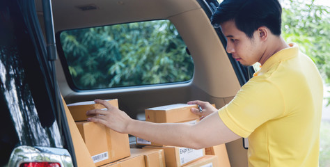 Young Asian Delivery man checking list of package boxes Fototapete