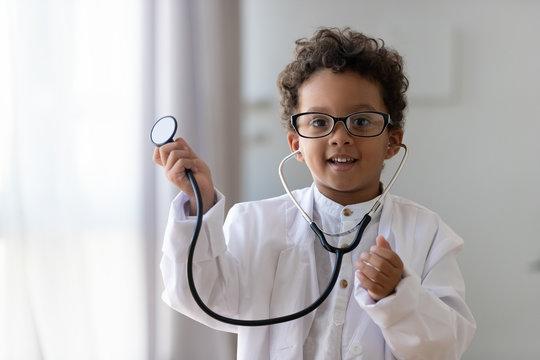 Cute african kid boy wear medical uniform playing doctor, portrait