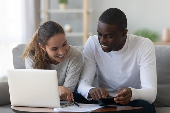 Happy smiling mixed race couple calculating domestic bills at home
