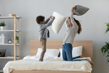 Mixed ethnicity mum and son enjoy pillow fight on bed