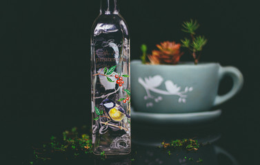 Olive oil bottle with ornate colorful bird design on black background with succulent plants in a tea cup