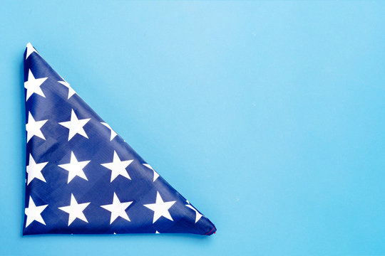 Folded USA flag on a blue background. Concept Memorial Day, Independence Day, July 4th. Flat lay, top view