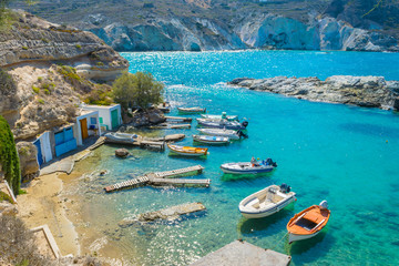 A small harbor with fishing boats and crystal clear turquoise waters in Mandrakia village in Milos island, Greece