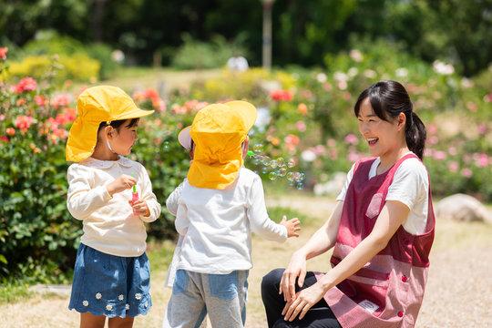 公園で遊ぶ保育士と園児たち