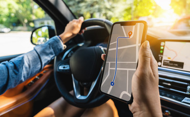 Tourist using GPS map navigation app on smartphone screen to get direction to destination address in the car, travel and technology concept image