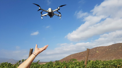 close up of dronE fliying with a hand trying to take it - beautiful landscape on the background with blue sky and green plants in mountain
