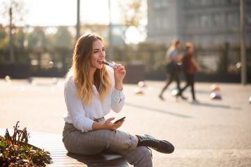Happy girl having bite of energy bar, candid shot. Fotoväggar