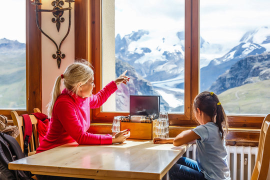 Mother and little daughter at the restaurant in the mountains with beautiful mountains view.