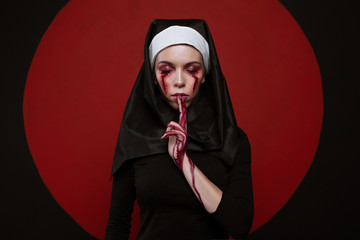 Satanic nun with bloody scar on face. Horror halloween concept. Sister prays with closed eyes