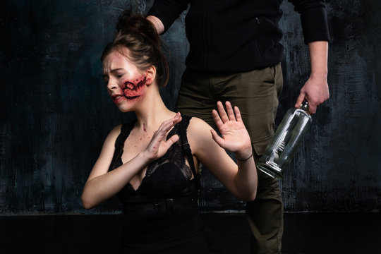 Domestic violence. Alcoholic husband hurts his wife and holding her hair. Makeup text mine