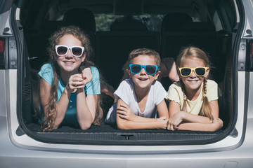 Happy brother and his two sisters are sitting in the car at the day time.