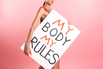 Image cropped of nice serious woman wearing white sexual lace lingerie holding placard with text isolated