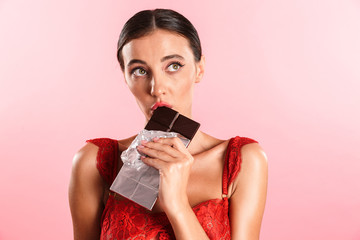 Closeup image of cute thinking woman wearing red sexual lace lingerie eating chocolate bar