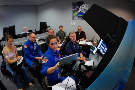 NASA commercial crew astronauts Nicole Mann and and Mike Fincke and Boeing astronaut Chris Ferguson run through scenarios in a simulation cockpit of the Boeing Starliner spaceship at the Johnson Space Center in Houston