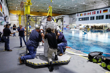 NASA Commercial Crew Astronaut Josh Cassada is helped to get into his space suit at NASA's Neutral Buoyancy Laboratory (NBL) training facility near the Johnson Space Center in Houston,