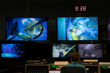 A control room full of video screens keeping watch over the underwater training at NASA's Neutral Buoyancy Laboratory (NBL) training facility near the Johnson Space Center in Houston,