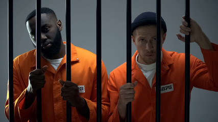 Caucasian and afro-american prisoners holding jail bars and looking to camera